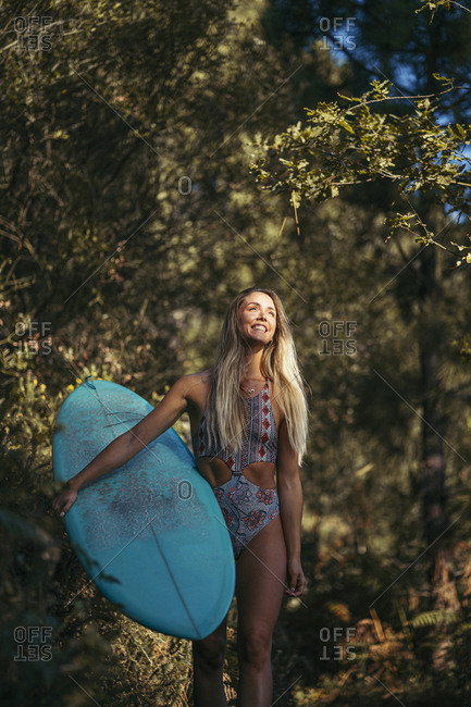 Young blond woman with a surfboard walking in the forest- looking up
