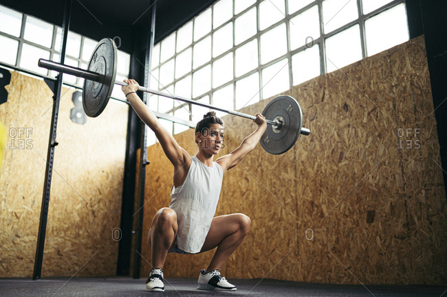 Young brunette woman doing overhead squat exercise at gym