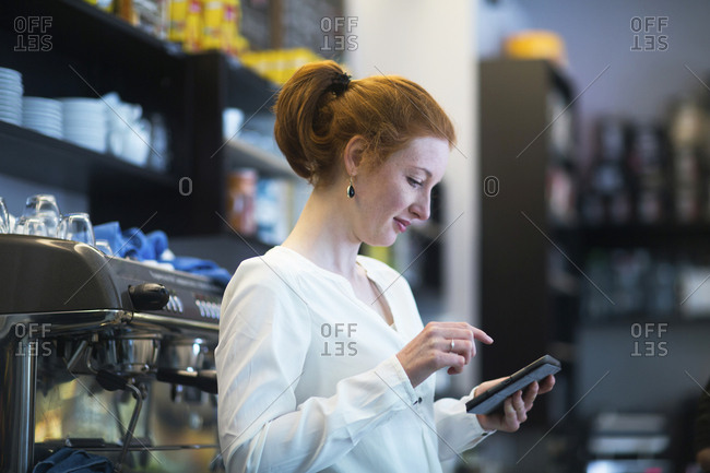 Young woman working in coffee shop- using calculator