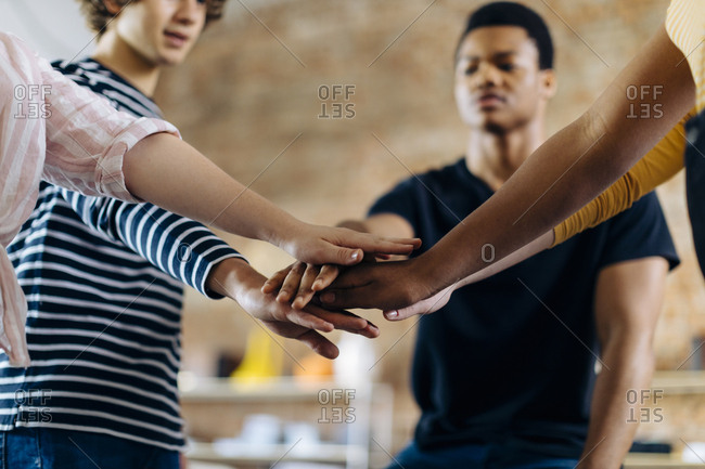 Young people standing together stacking hands
