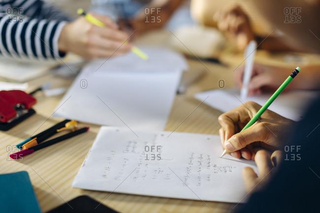 Close-up of young man writing down formula