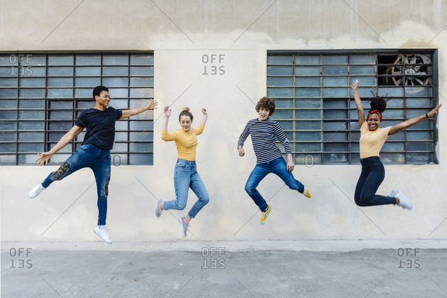 Exuberant friends jumping outdoors
