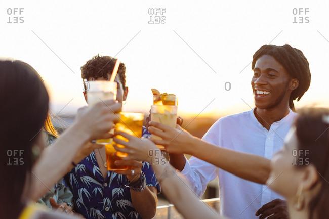 Happy multi-ethnic friends toasting drinks