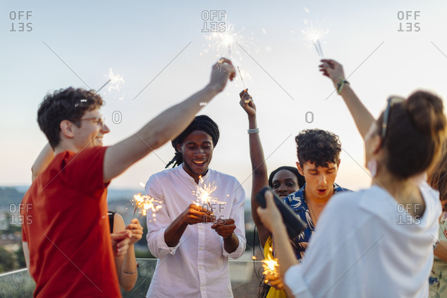 Group of happy multi-ethnic friends celebrating a party in the evening- holding sparklers
