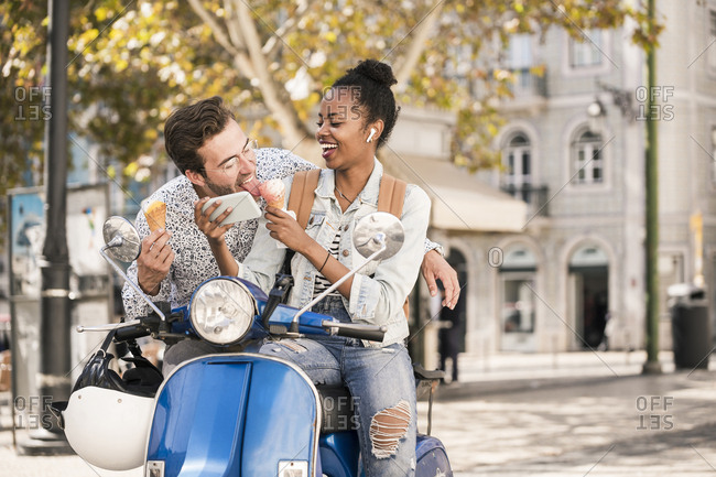 Happy young couple with motor scooter- ice cream and mobile phone in the city- Lisbon- Portugal