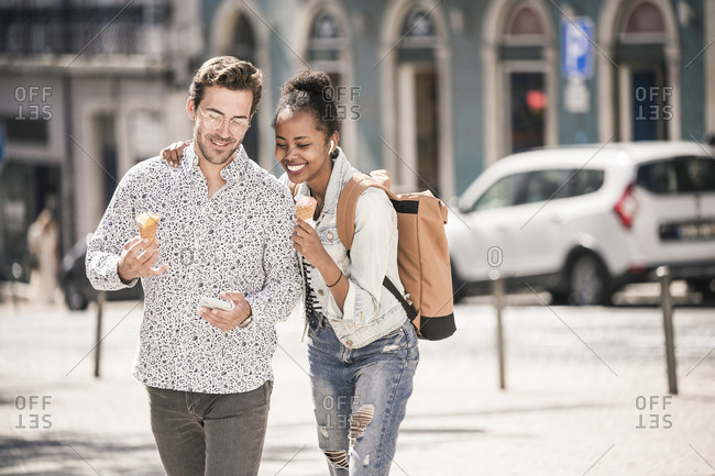 Happy young couple with ice cream and mobile phone in the city on the go- Lisbon- Portugal
