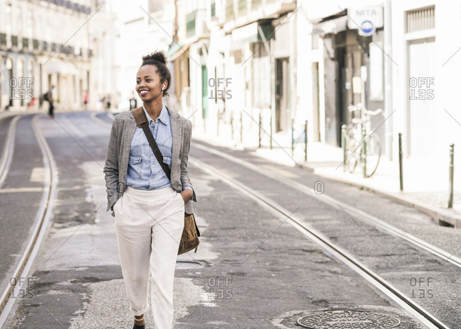 Smiling young woman with wireless earphones in the city on the go- Lisbon- Portugal