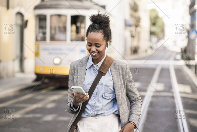 Smiling young woman with earphones and mobile phone in the city on the go- Lisbon- Portugal
