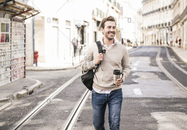 Smiling young man with backpack and coffee mug in the city on the go- Lisbon- Portugal