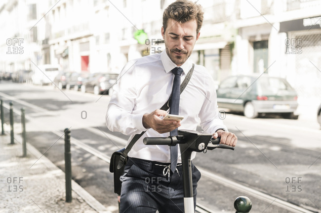 Young businessman with e-scooter using mobile phone in the city- Lisbon- Portugal