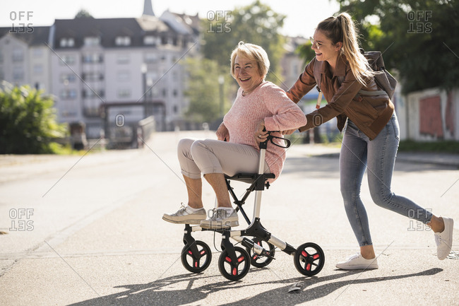 Granddaughter and her grandmother having fun with wheeled walker