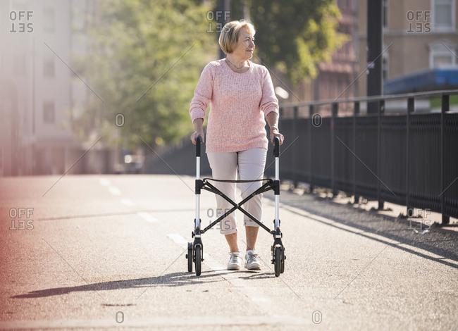 Senior woman with wheeled walker on footbridge