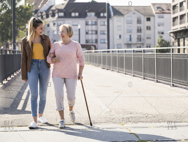 Granddaughter and her grandmother walking on footbridge