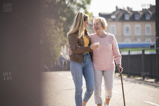 Granddaughter and her grandmother walking on footbridge and using smartphone