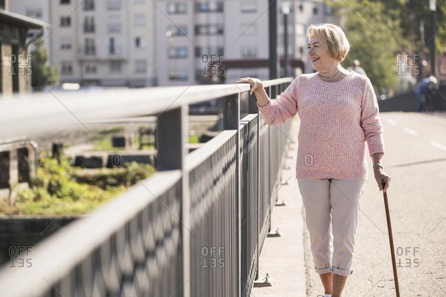 Senior woman walking on footbridge- using walking stick- looking away