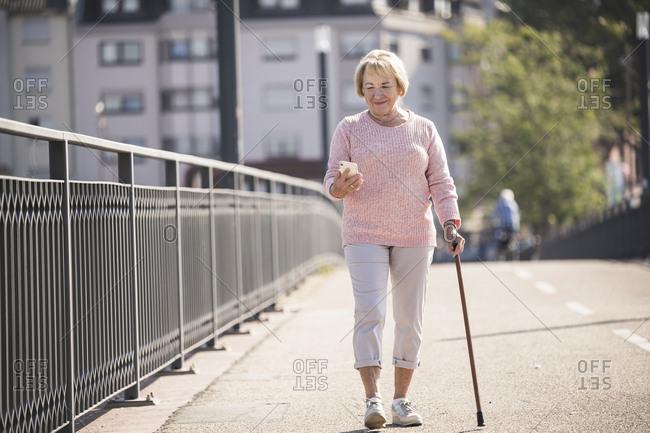 Senior woman walking on footbridge- using walking stick