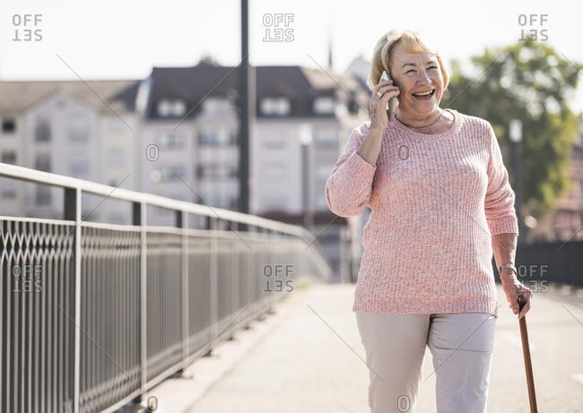 Senior woman walking on footbridge- using walking stick and phoning