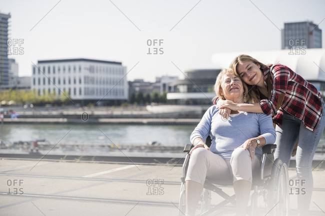 Young woman head to head with her laughing grandmother sitting in wheelchair