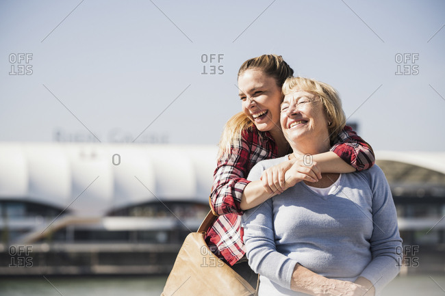 Young woman embracing her smiling grandmother sitting in wheelchair
