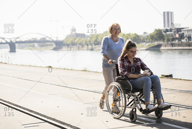 Grandmother with her granddaughter sitting in wheelchair
