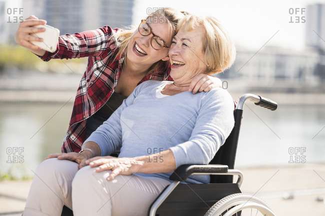 Young woman with her smiling grandmother sitting in wheelchair and taking a selfie