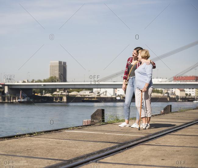 Granddaughter and her grandmother walking on riverside