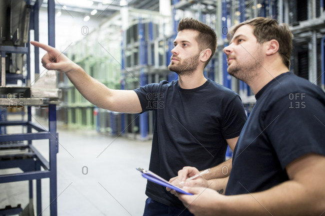 Worker with colleague in factory warehouse pointing his finger