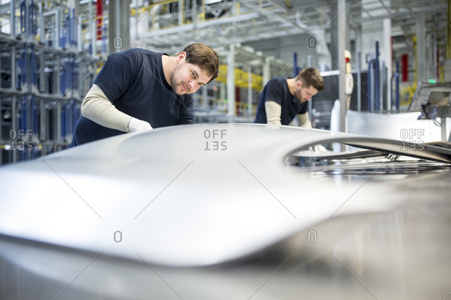 Two colleagues examining bonnet in car factory
