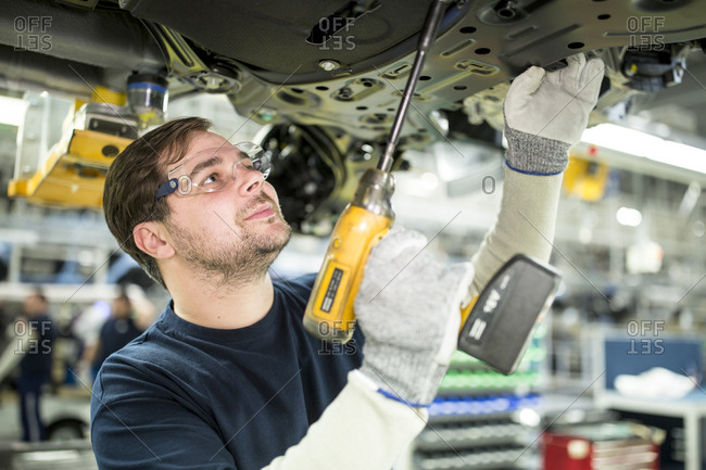 Man working at car underbody in modern factory