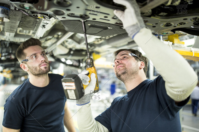 Two colleagues working at car underbody in modern factory