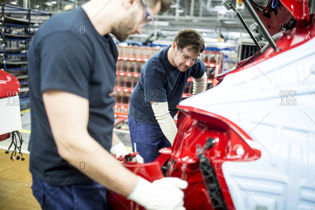Two colleagues working in modern car factory