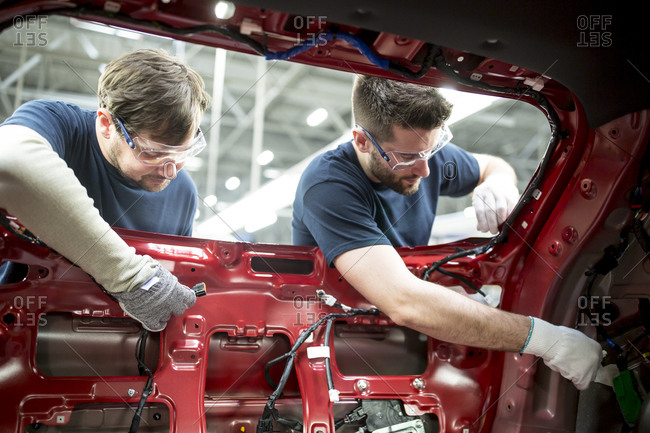 Two colleagues working at bodywork in modern car factory