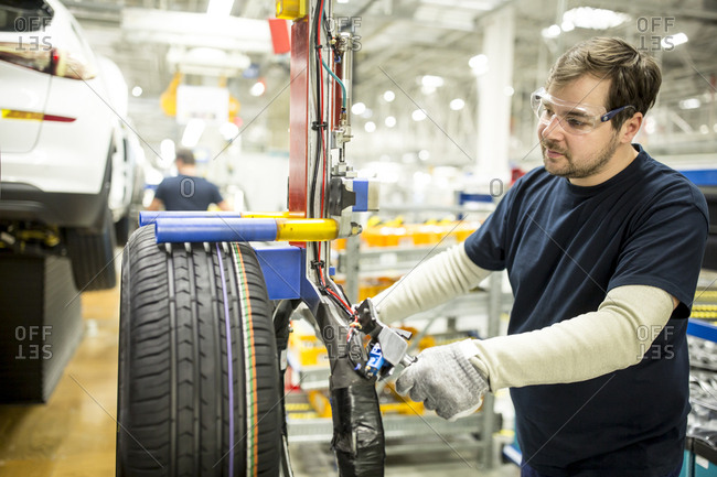 Man working on tire in modern car factory
