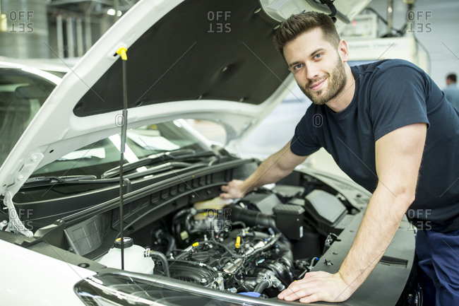 Portrait of confident man working on car in modern factory