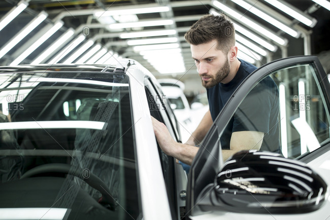 Man working in modern car factory wiping finished car