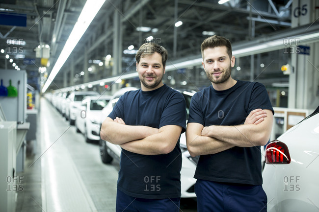 Portrait of confident colleagues in modern car factory