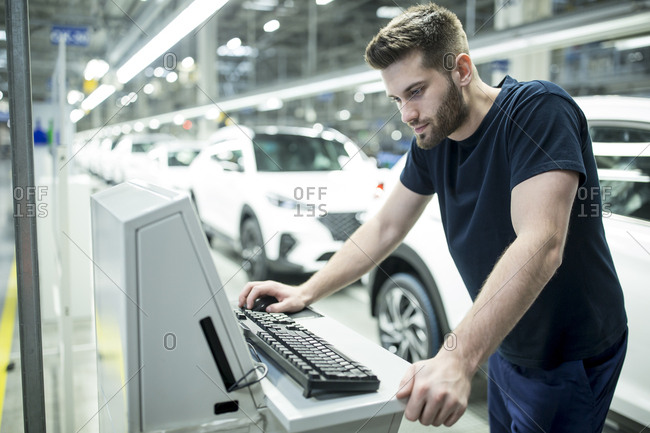 Man working on computer in modern car factory