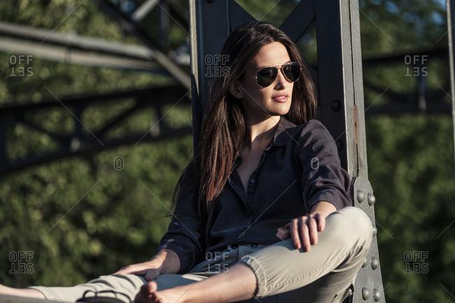 Young woman enjoying the evening sun- sitting on a bridge