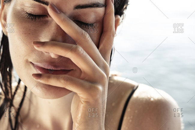 Woman with eyes closed and hand on her face after bathing- close-up