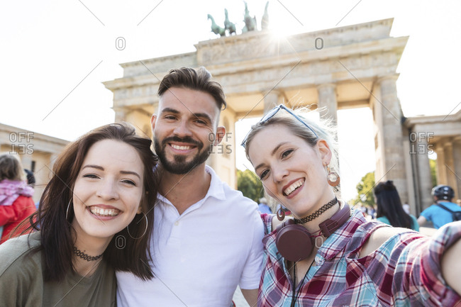 Portrait of three happy friends taking selfie with cell phone in front of Brandenburger Tor- Berlin- Germany