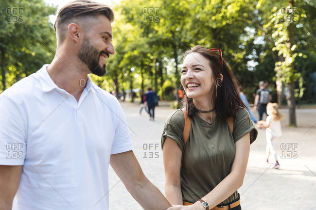 Portrait of happy young woman walking hand in hand with her boyfriend in a park