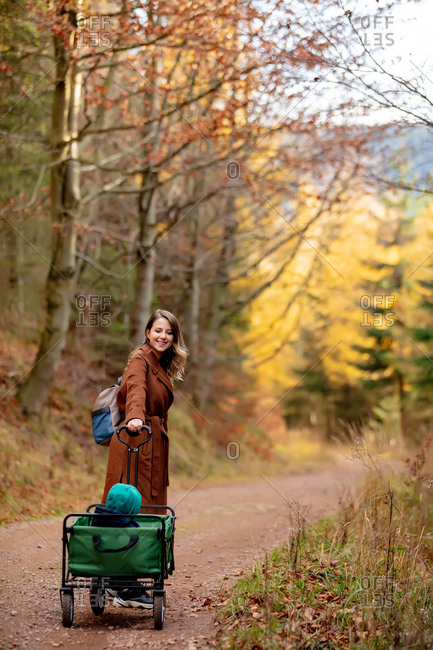 Woman with a child in a wagon walking through a forest