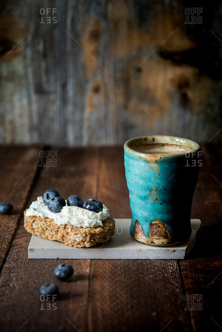 Cup of coffee with a slice of whole meal bread with ricotta cheese and blueberries