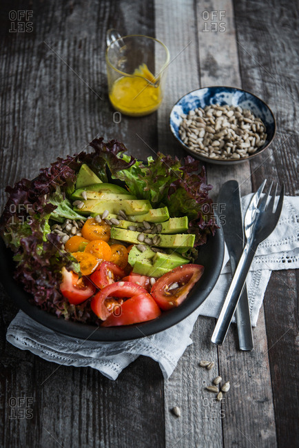 Fresh avocado salad with sunflower seeds and mustard dressing on wooden background