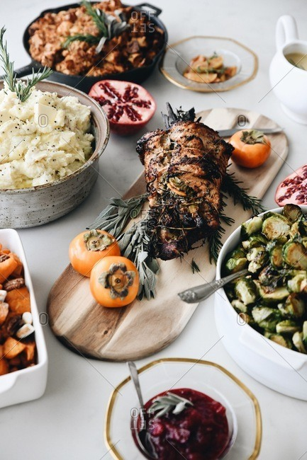 Thanksgiving spread on a white table with a roast and side dishes
