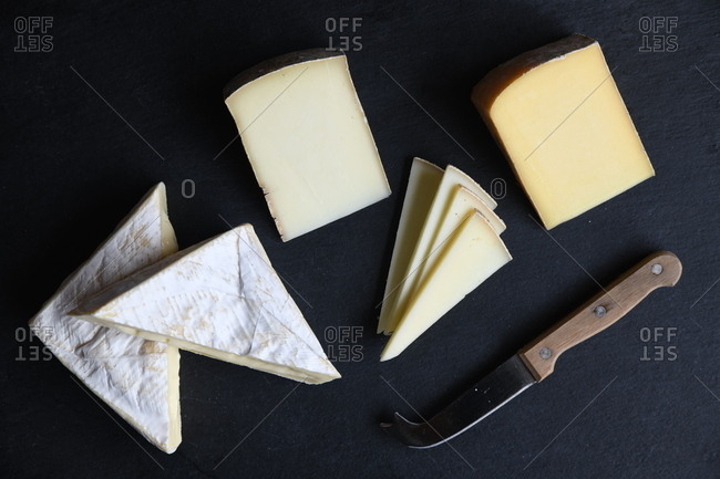 Variety of cheeses on black background with knife
