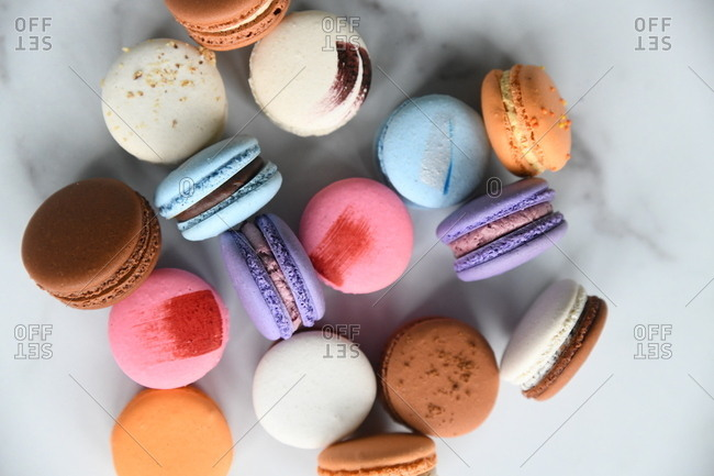 Overhead view of colorful macaron cookies on marble surface