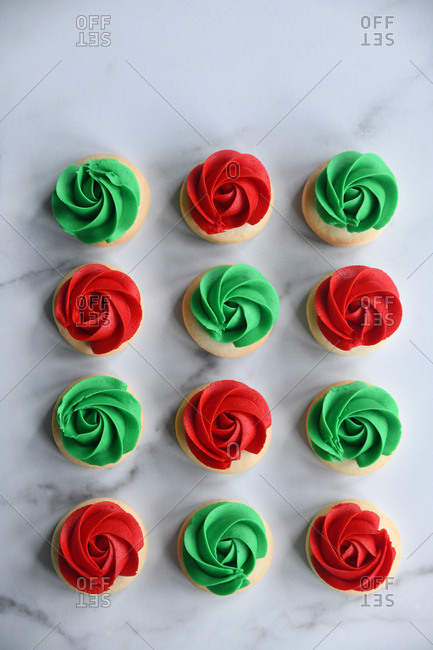Red and green frosted sugar cookies on marble surface