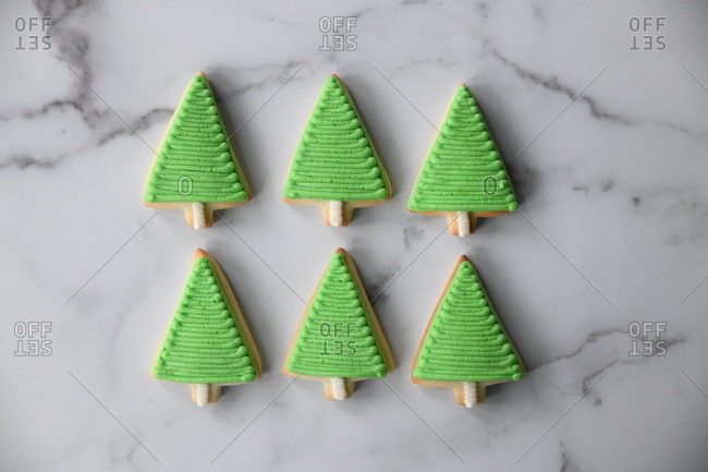 Green frosted tree sugar cookies on marble surface
