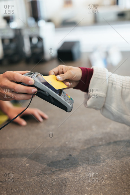 Woman paying with the contactless payment option while paying for coffee